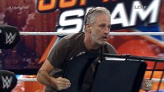 While 'Arrow' star Stephen Amell performed admirably in his WWE in-ring debut, it was SummerSlam host Jon Stewart who played the biggest role in one of the biggest matches of the night. Stewart opened Sunday's show at Barclays Center in Brooklyn sporting a retirement beard and a lot of enthusiasm. WWE champion Seth Rollins and U.S. champion/'Trainwreck' actor John Cena were squaring off in a great title-for-title match when the former 'Daily Show' host made his mark.