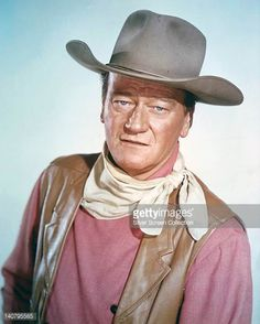 John Wayne US actor wearing a tan leather waistcoat a pink shirt and a white neckerchief in a studio portrait against a light blue background circa...