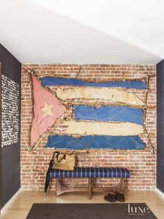 Artist Kcho's Cuban flag, made to look like makeshift rafts, not only nods to the owner's heritage but is also a commentary on emigration. It hangs above a Kravet fabric-wrapped 1960 Adrian Pearsall bench from Hamptons Antique Galleries. A rolling paper work by Jac Leirner is at left.