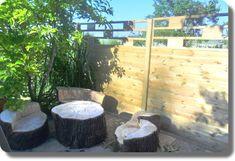 Sichtschutzzaun mit Zierelement im Garten hinter einer Sitzgruppe mit Baum
