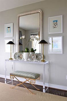 Chic Foyer Features A Pair Of Seagrass Baskets Tucked Under A Clear Acrylic  Console Table, CB2 Peekaboo Console Table, Topped With A White Orchid Pu2026
