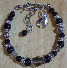 "I have designed these awareness bracelets in recognition of our friends and family that have or are currently fighting cancer. This 7.75"" black bracelet represents Melanoma. This bracelet is designed with fiber optic beads, Swarovski crystals and crystal rings and silver designer beads and findings. It is finished off with a hook fastener, 1.5"" extension chain and a 1"" silver awareness ribbon."