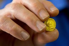 Israeli Antiquities Authority official Donald T. Ariel holds a rare, nearly 2,000-year-old gold coin... - AP Photo/Ariel Schalit