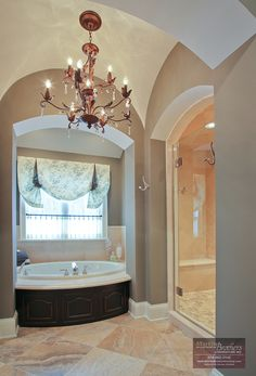 The gorgeous copper chandelier is the centerpiece of this master bath
