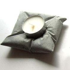 Deceptive concrete design - collection of soap dishes and candleholders from concrete moulded in plastic bags.