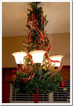 Christmas Chandelier Makeover. Wire a greenery wreath to the bottom of the chandelier, then wiring greeneryfrom the top of the chandelierchain tothe middle of the chandelier...Next attaching ornaments at random spacing, adding berries and some wire edged ribbonsfrom the top. Wire edged ribbon allows you to curl the ribbon for the effect shown. christmas-home-decor