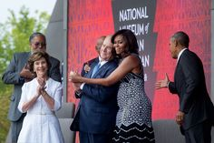 """Sept. 24, 2016 """"The First Lady hugs former President George W. Bush as she and President Obama take the stage during the opening ceremony of the Smithsonian National Museum of African American History and Culture in Washington, D.C."""" (Official White House Photo by Chuck Kennedy)"""