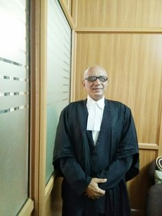 Advocate Jayaprakash Mallay in his Office in full attire with the Robe and the Collar band.