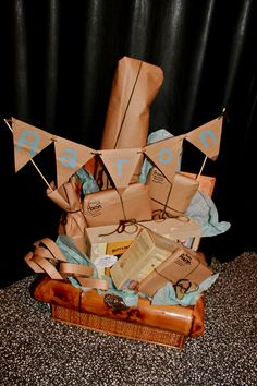 Safari themed baby shower gift: Presents wrapped in inside out paper brown bags and baby name banner made out of brown bags and kabob sticks....
