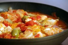 Ling cod fillets cooked in onions, green olives, tomatoes and orange slices.
