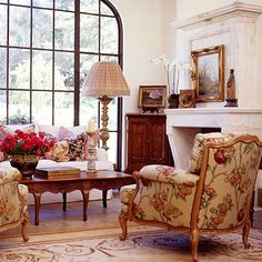 A conversation area in front of a striking fireplace is accented with a corner chest near the window. Oil paintings on the mantel and on the...