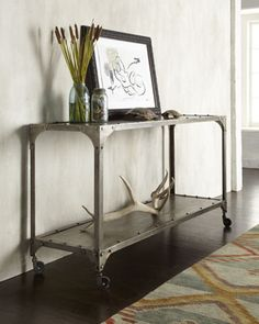 "$1400    Urban-chic console table offers mobile storage options.  Constructed of solid iron.  Acid-wash nickel-chrome finish.  Four industrial-style casters.  59""W x 18""D x 31""T.  Imported."