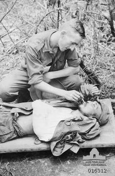 New Guinea. December 1943. Private G. Hull of North Melbourne, Vic, lights a cigarette for a wounded Japanese prisoner of war (POW), lying on a stretcher at a mobile surgical team's headquarters at Kumbarum.