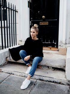 """ゆったりサイズの黒ニットとデニムに白スニーカーを合わせたシンプルなコーディネートです。デニムをロールアップすることで、脱カジュアルの""""こなれ感""""が出ていますね。"""