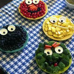 Sesame Street fruit & veggie plates with dip. cookie monster, elmo, big bird, oscar, tomatoes, brocoli, pineapple, blue berries, carrots.