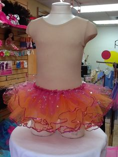 Sequined Tutu in Orange and Pink $17.99. Perfect for Dress-up or dance class. Matches perfectly with a mulberry colored leotard. One Size Fits Most. For more information or to check availability, call or email Polka Dots. 916-791-4496. polkadotsproshop@gmail.com
