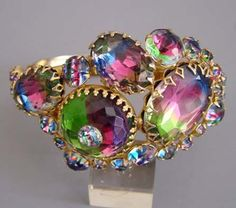 """JULIANA style unsigned gold tone hinged bangle with pink, green and blue striped rhinestones (called IRIS stones), one with an inset rhinestone, several with multiple decorative prongs,  6-3/4"""" by 1-3/4"""" front."""