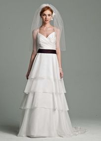 Tiers are a top bridal gown trend, and this gown features an elegant interpretation. A-line skirt is designed with layers of soft organza tiers to create a beautiful drape and shape. Satin spaghetti strap bodice features a surplice, pleated neckline that is flattering on many body types. A subtle satin band accents the waist and the back features a very feminine V-neck and chapel train. Available in Ivory or White. Fully lined. Back zip. Imported polyester. Dry clean.