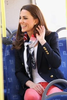 A navy blue blazer with a silk scarf, a white tee, and coral jeans. Catherine, Duchess of Cambridge.