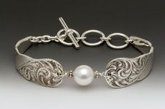 "This scrolled silver spoon bracelet features a white Swarovski pearl and the look of an antique silver pattern. length: 6 1/2"" - 8"" adjustable width: 5/8"" silver plate silver fill toggles Made in the"