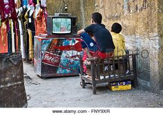 CAIRO, EGYPT - JUL 23:  Children sitting in the middle of the street watching tv, streets of Khan El Khalili bazaar, - Stock Photo