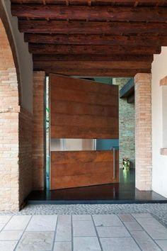 O puxador mais baixo que o padrão deu personalidade a essa porta pivotante de madeira. Fotografia: http://www.decorfacil.com/portas-pivotantes/