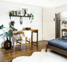 While the simple Scandinavian wood furniture in this bedroom-slash-office could come off as cold, the homeowner warmed it up with living greens and soft sheepskin throws.