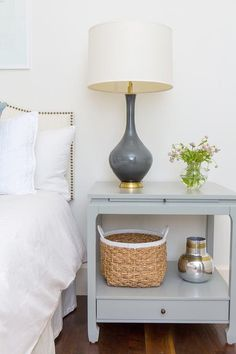 Chic bedroom boasts a cream nailhead curved nightstand dressed in white linen bedding next to a light gray nightstand and a dark gray lamp.