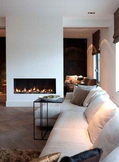 Prachtige haard in het midden van de woonkamer met een stijlvolle bank waar je gezellig op kan zitten bij het vuur | Wonderful fire place in the middle of the living room with a stylish couch