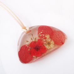 Pendentif Amaryllis galet en résine fleurie