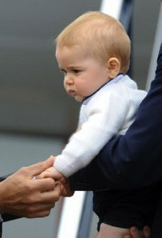 Prince George's hand is held by New Zealand Governor General Jerry Mateparae as he leaves with his parents Prince William and Kate, the Duchess of Cambridge on a plane bound for Sydney, Australia from Wellington, NZ, 16 April 2014.