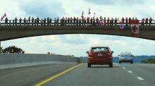 Canadians line overpasses along the Highway of Heroes to pay their respects to the fallen soldiers who pass.