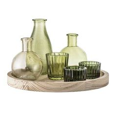 Bloomingville Green Glass Votive Collection with a Wooden Tray adds style in an instant. With this fantastic set of green glass vases and candleholders atop a round Paulownia wood tray.