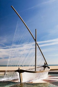 Wonderful piece of public sculpture placed at the Comunidad de Valencia is a sculptural fountain Located at Playa de la Malvarrosa in Valencia, Spain that uses streams of water to mimic the form of a traditional sailboat