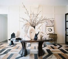 Geometric floors and a gathering of white busts and sculptures adorn Kelly Wearstler's chic office entry.