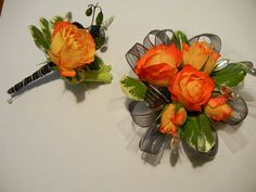 What in Carnation Floral Designs by Kristina Orange red corsage with roses, lisianthus, and variegated pittosporum