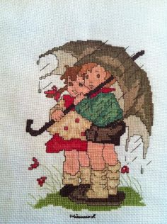 "A Bertha Hummel cross stitch called 'Umbrella Kid's"" that I finally completed after finding the right colored floss. Has classic German attire and feel to the collection I'm working on"