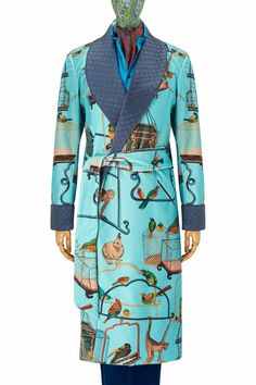 The scene on this stunning velvet gown depicts various exotic animals in a menagerie. The rich turquoise of the gown is beautifully contrasted by the deep blue silk quilted revers. It is piped throughout in navy and is fully lined in a rich two-tone turquoise and fuchsia satin. It is handmade in England.