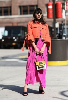 Street-styler wearing a crinkle pink skirt and fuchsia jacket at NYFW | ASOS Fashion & Beauty Feed