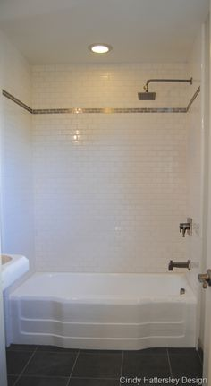 Resurface tub. Subway tile and stainless steel tile accent from Home Depot. Charcoal ceramic tile floor.