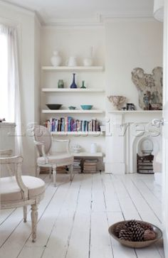 Contemporary shelving in room with bare painted floorboards London townhouse England UK. White Painted Wood Floors, Painted Floorboards, White Wooden Floor, White Floorboards, White Flooring, White Wood Shelves, White Washed Floors, Living Room White, White Rooms