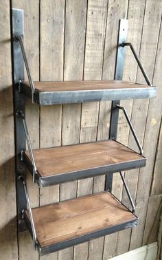 three tier wall mounted shelves two sets of steel and timber wall mountedshelving frames feature a mix of flat, angle and round bar steel, the timber shelves are infilled flush to the tops of the angle surrounds. £0.00