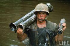 American Marine Phillip Wilson carrying bazooka through a stream during a patrol near the DMZ. Vietnam, 1966, Photographer:Larry Burrows