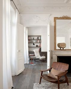 Love the rustic flooring with the ornate antique mantel and moldings and modern furnishing.