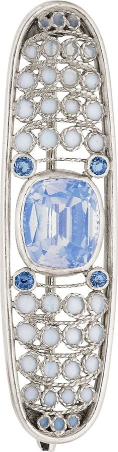 An Arts and Crafts moonstone, montana sapphire, plique-à-jour enamel and platinum brooch, Tiffany & Co., circa 1907. The brooch featuring a faceted cushion-shaped moonstone, enhanced by round-shaped Montana sapphires, accented by opalescent plique-à-jour enamel, set in platinum, marked Tiffany & Co., likely designed by or under the direction of L.C. Tiffany. 1-13/16 inches.