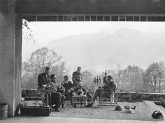 The wider frame view of Major Richard Winters, Captain Lewis Nixon, Lieutenant Harry Welsh (of the Band of Brothers) and two other men celebrating V-E Day on the patio at Hitler's alpine retreat in Berchtesgaden (May 8, 1945). The men had their first choice of a captured, extensive wine collection originally assembled at Hermann Göring's orders, comprising bottles which were stolen from wineries across France and other occupied territories. The helmet at right bears the Easy Company spade…