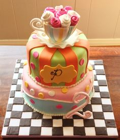 """Two tiered """"tea party"""" mad hatter cake, covered in all fondant. Teacup topper contains a smash cake for the birthday girl!"""