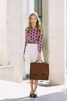Printed blouse, white pleated skirt, loafers, and briefcase.