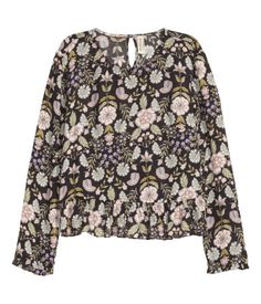 Long-sleeved blouse in airy, crêped woven fabric. Opening at back of neck with button, small ruffle at cuffs, and flounce at hem.