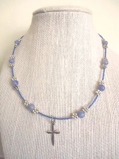 Need a bit more teal in your life?  This soothing choker-length necklace was hand-crafted from teal blue glass beads and natural blue aventurine, accented with dainty silver-plated flower fittings and paired with a simple Christian cross charm as a pendant.  Enjoy :)